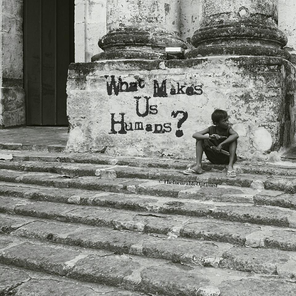 Picture of a boy sitting in front of an old church