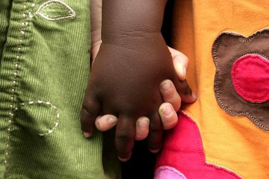 A black and white child hold hands