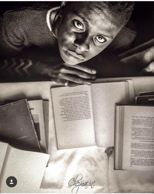 Portrait of a Boy looking at the camera with a pile of book on his desk